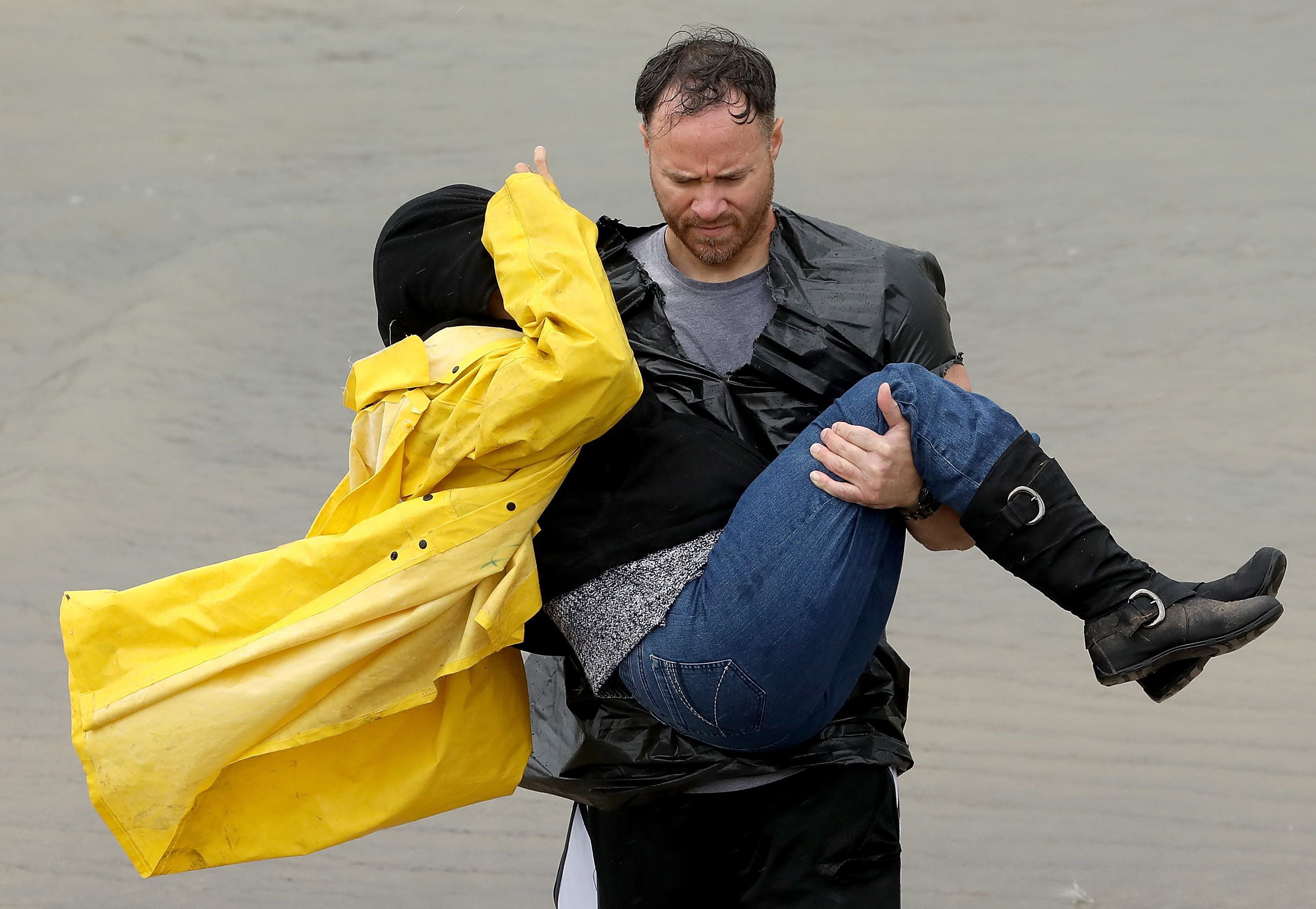 A volunteer carries a woman whose home was affected by severe flooding in north Houston.