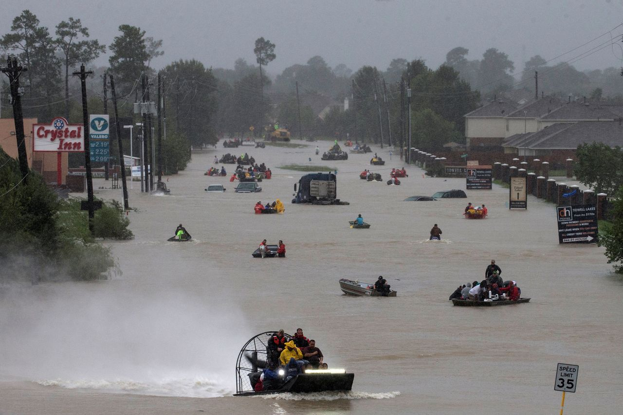 Residents use boats to evacuate from Tropical Storm Harvey along Tidwell Road in east Houston on Aug. 28.