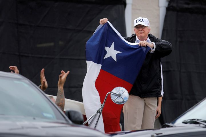 U.S. President Donald Trump holds a flag of the state of Texas after receiving a briefing on Tropical Storm Harvey relief eff