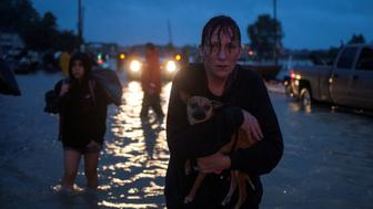 A woman holds her dog as she arrives to high ground after evacuating her home due to floods caused by Tropical Storm Harvey along Tidwell Road in east Houston, Texas, U.S. August 28, 2017. REUTERS/Adrees Latif     TPX IMAGES OF THE DAY