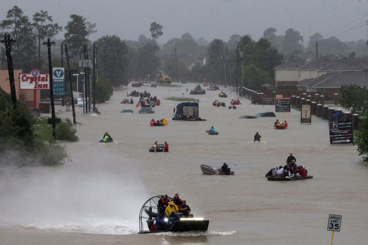 Residents use boats to evacuate flood waters along Tidwell Road east Houston, Texas, on Monday.