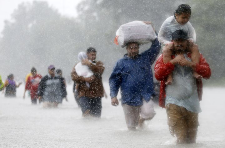 Residents wade through flood waters from in Beaumont Place, Houston, on Monday.