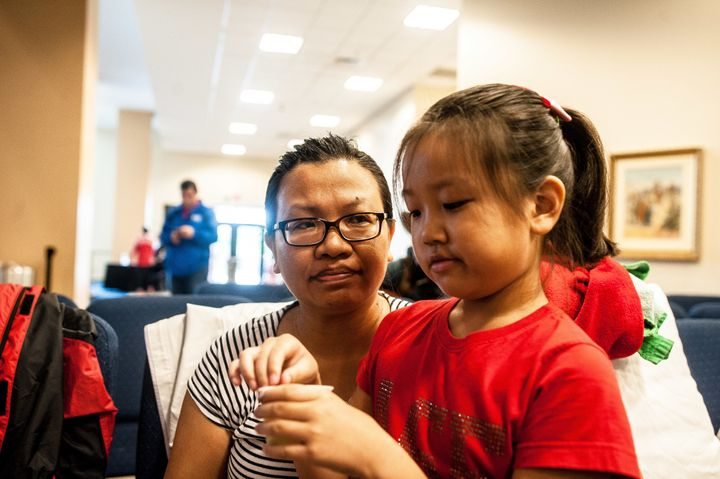 Jie Zhang, 38, and her daughter Sheryl, 8, wait to be entered into the shelter at Lakewood Church in Houston.
