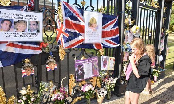 Flowers and tributes begin to appear at the gates of Kensington