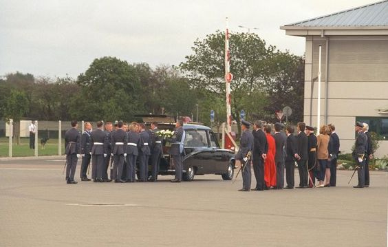 The coffin is carried off the plane at RAF