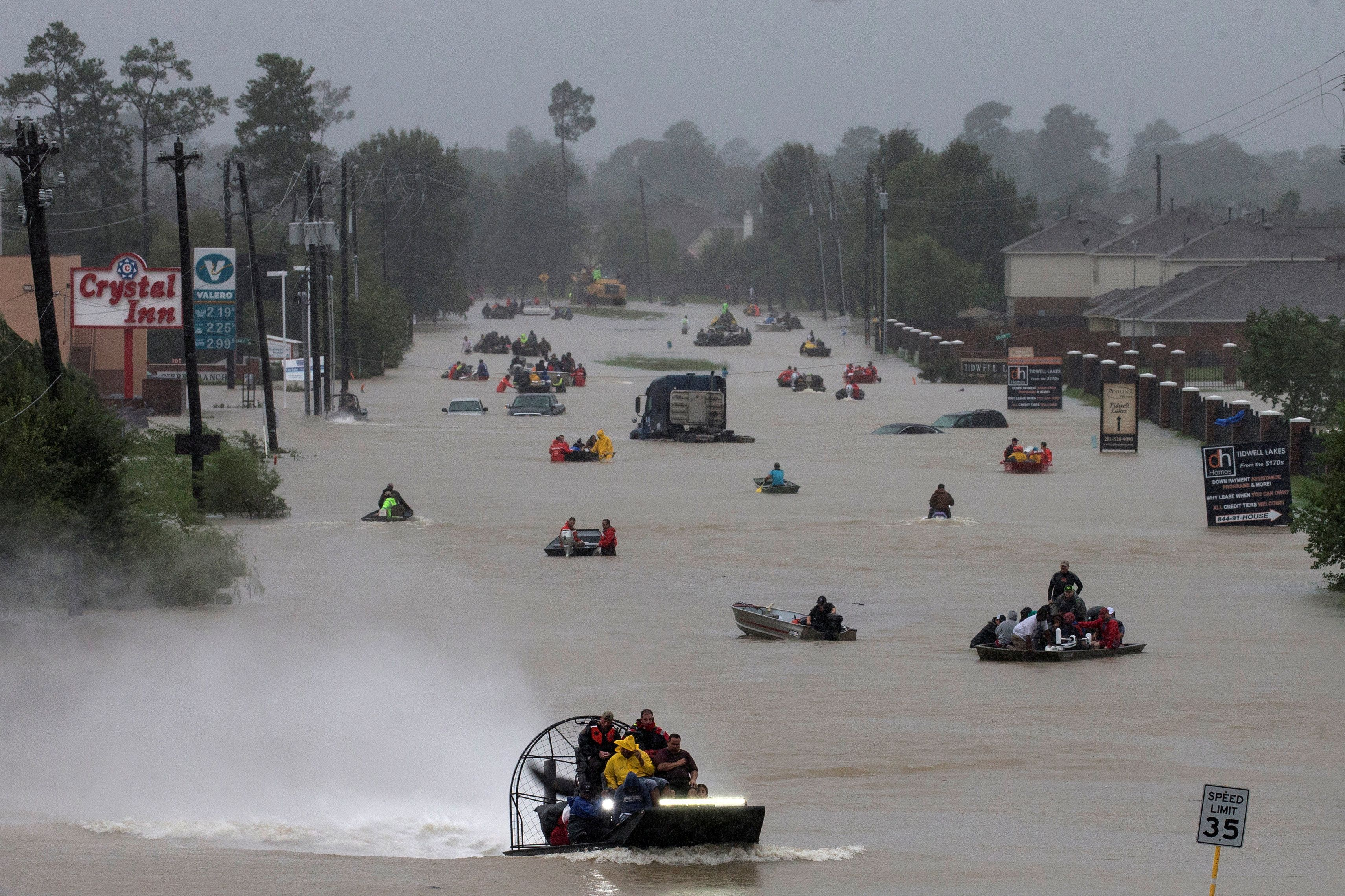Residents use boats to evacuate flood waters from Tropical Storm Harvey inHouston, Texas, Monday.