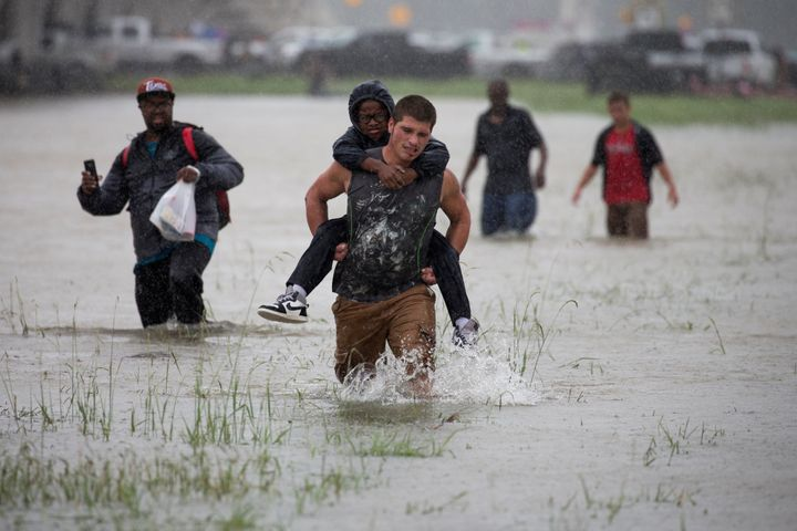 A man wades through flood waters from Tropical Storm Harvey while helping evacuate a boy in east Houston on Monday.