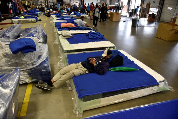 Evacuees get some rest in the warehouse at Gallery Furniture which opened its doors to residents needing shelter, in Houston,