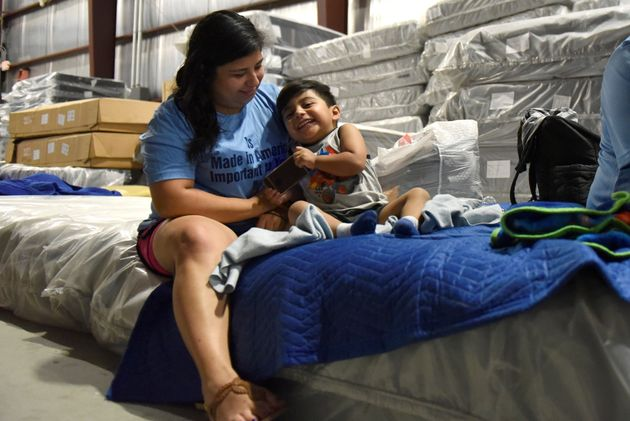 Maria Lopez plays with her son Rafael Lopez, 3, in the Gallery Furniture warehouse where they have been...