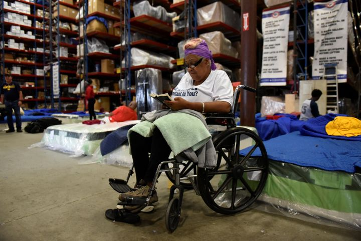 Charlotte Mills reads her Bible in Gallery Furniture's warehouse on Tuesday after evacuating her flooded home.