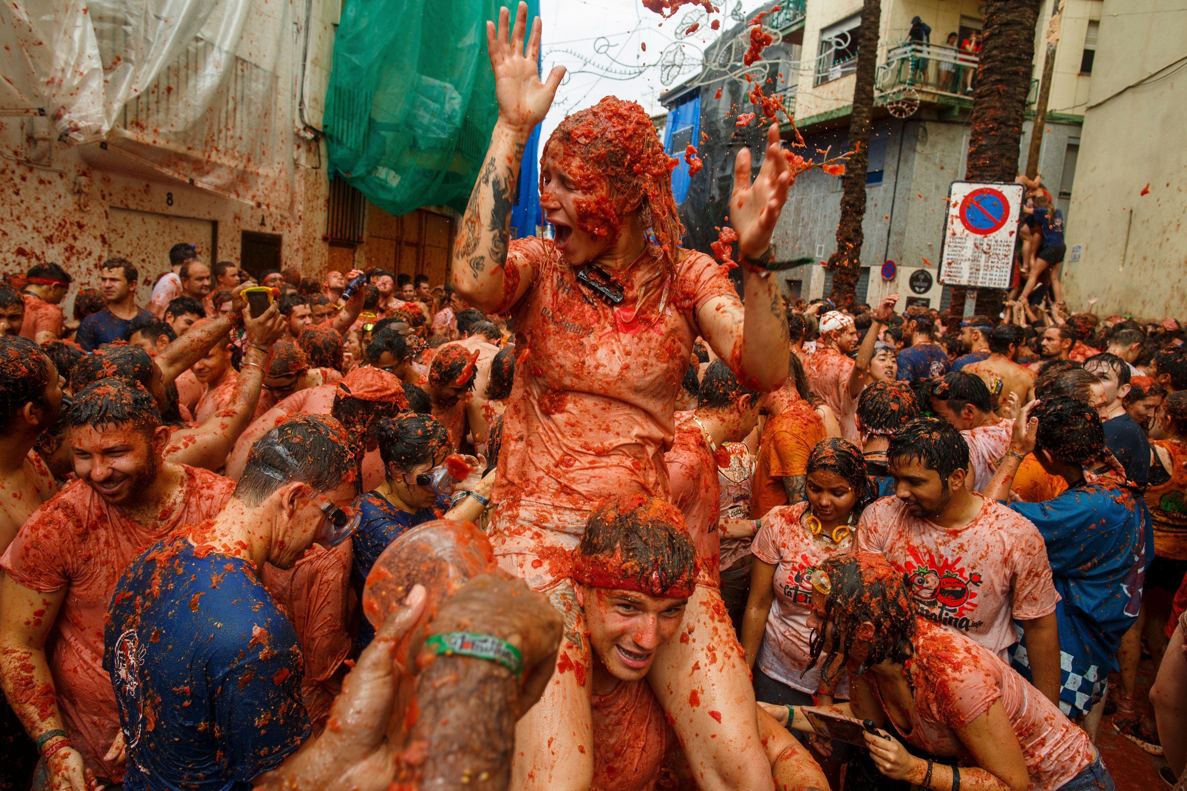 BUNOL, SPAIN - AUGUST 30:  Revellers enjoy the atmosphere in tomato pulp while participating the annual Tomatina festival on August 30, 2017 in Bunol, Spain. An estimated 22,000 people threw 150 tons of ripe tomatoes in the world's biggest tomato fight held annually in this Spanish Mediterranean town.  (Photo by Pablo Blazquez Dominguez/Getty Images)