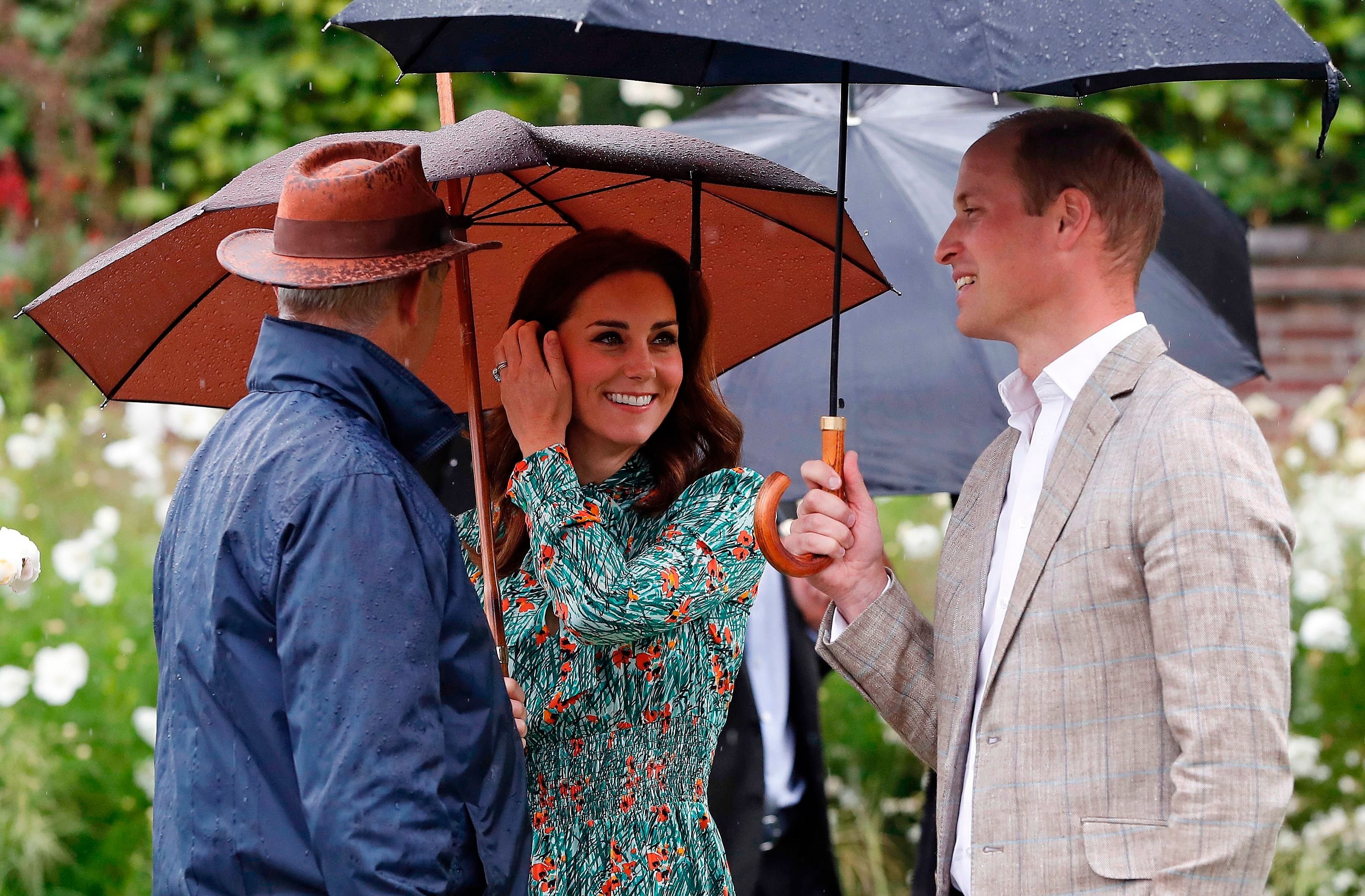 Britain's Prince William, Duke of Cambridge (R), and his wife Britain's Catherine, Duchess of Cambridge (C), shelter from the rain beneath umbrellas as they attend an event at the memorial gardens in Kensington Palace, west London on August 30, 2017. Princes William and Harry prepared to pay tribute to their late mother Princess Diana on Wednesday for the 20th anniversary of her death as wellwishers left candles and flowers outside the gates of her former London residence. The Princes visited the Sunken Garden in the grounds of Kensington Palace, which this year has been transformed into a White Garden, dedicated to their late mother, Britain's Diana, Princess of Wales. / AFP PHOTO / POOL / Kirsty Wigglesworth        (Photo credit should read KIRSTY WIGGLESWORTH/AFP/Getty Images)