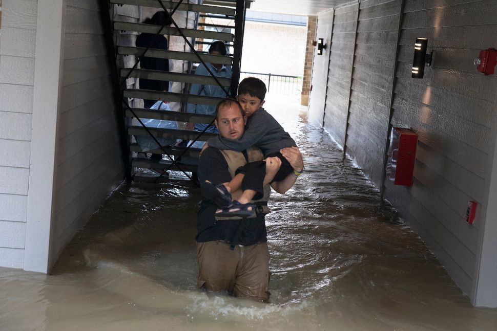 Volunteer Dustin Langley, who lives two hours north of Houston and came down with a friend to volunteer, helps a family to es