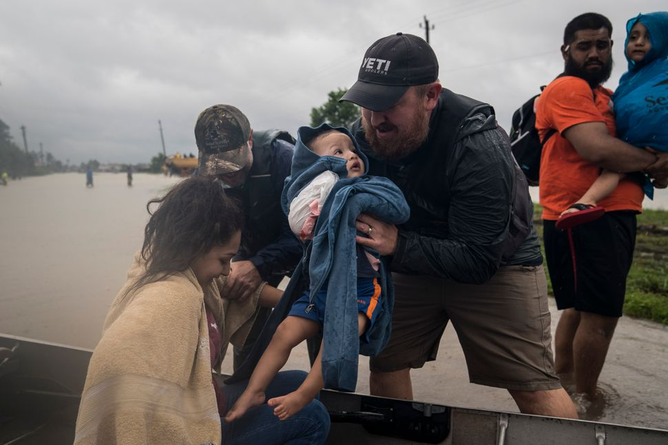 Glenda Montelongeo, Richard Martinez and his two sons are helped out of a boat after being rescued near Tidwell Road and Toll