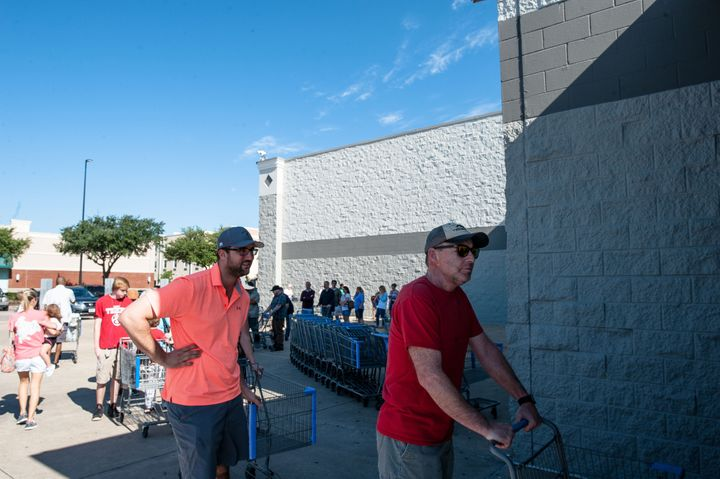 People wait in line to get into Wal-Mart in Katy, Texas on Wednesday.