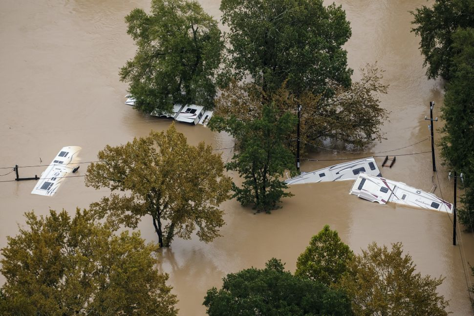 Recreational vehicles lie on their sides in the floodwaters.