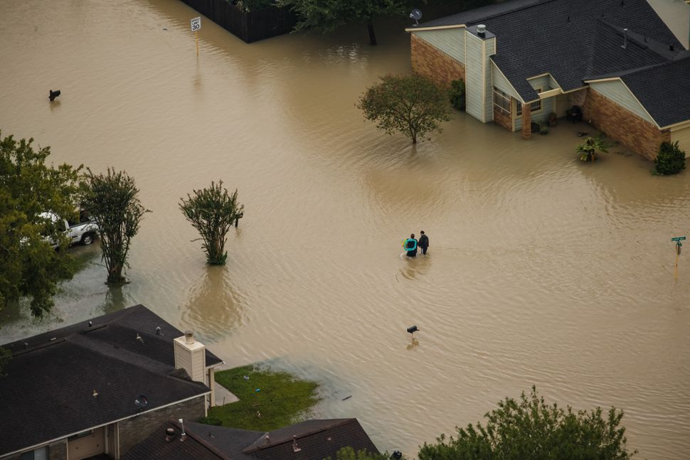 People walk through flooded neighborhoods.