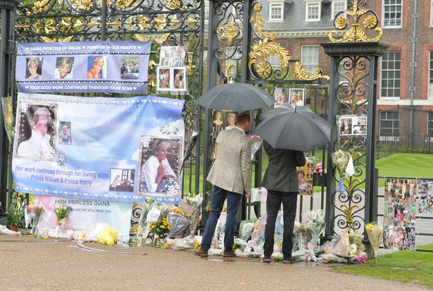 The Duke of Cambridge (left) and Prince Harry look at tributes to Diana, Princess of Wales attached to...