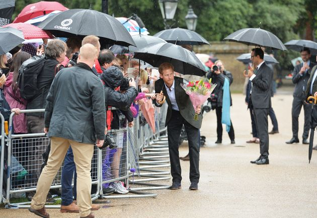 Prince Harry takes a bouquet of flowers from a wellwisher to add to the tributes to