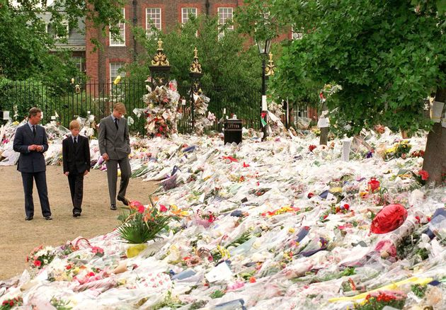 Prince Charles, Prince of Wales, Prince William and Prince Harry look at floral tributes to Diana, Princess...