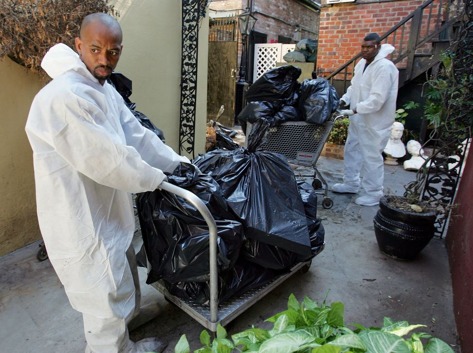 Following Katrina, Cedric Harrell (left) and Tom Miller remove spoiled food from the freezer at Court of Two Sisters restaura