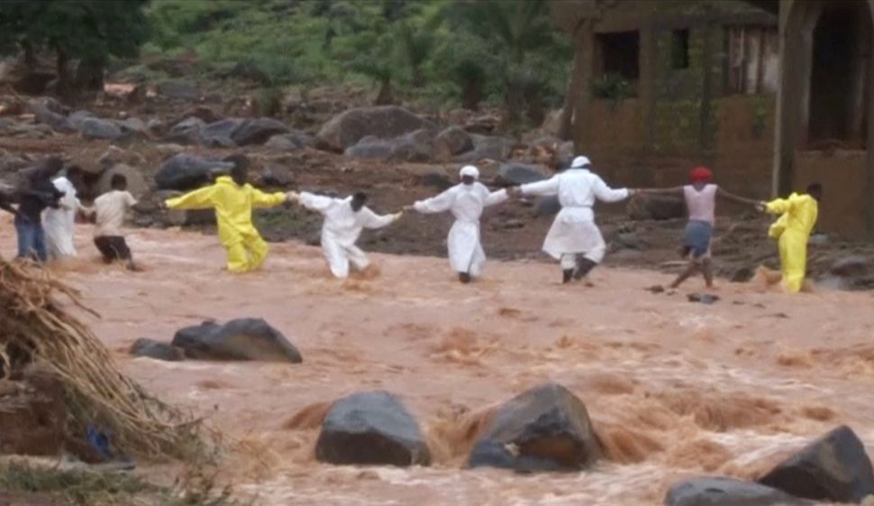People wearing protective suits hold hands as they cross a river after a mudslide in the mountain town of Regent on Aug.