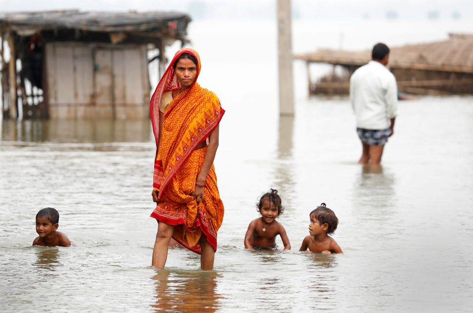 A woman walks through a flooded village in Motihari on Aug. 23.