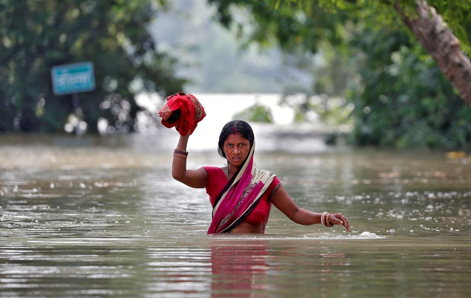 A woman wades through a flooded village in Bihar State on Aug. 22.