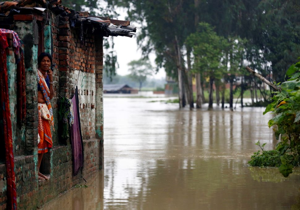 A woman looks out from her house in a flooded area of the city of Janakpur on Aug. 13.