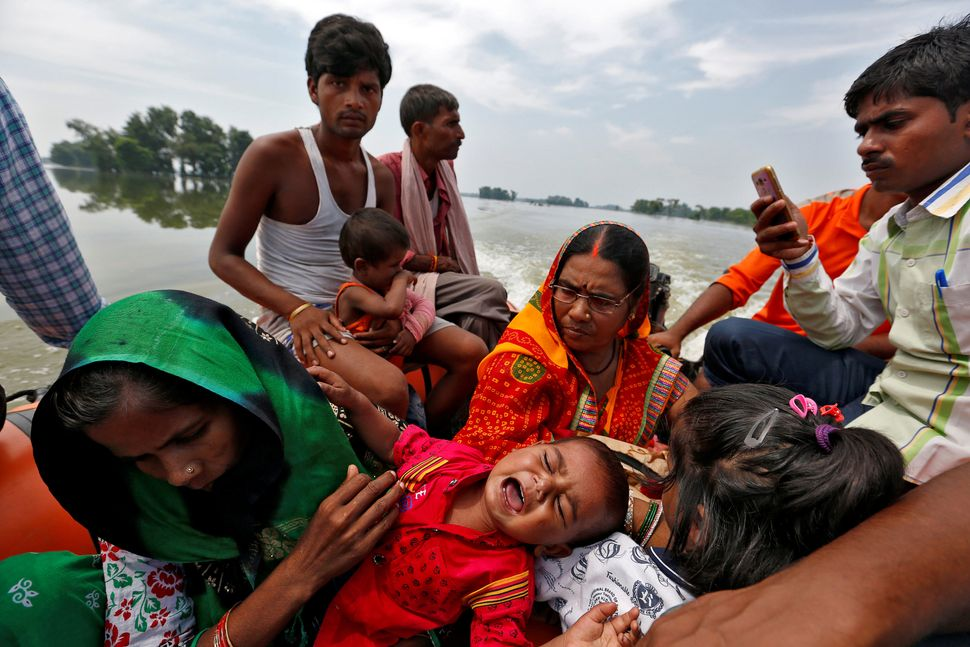 A baby suffering from dehydration cries after being rescued from a flooded village in Bihar State on Aug. 23.