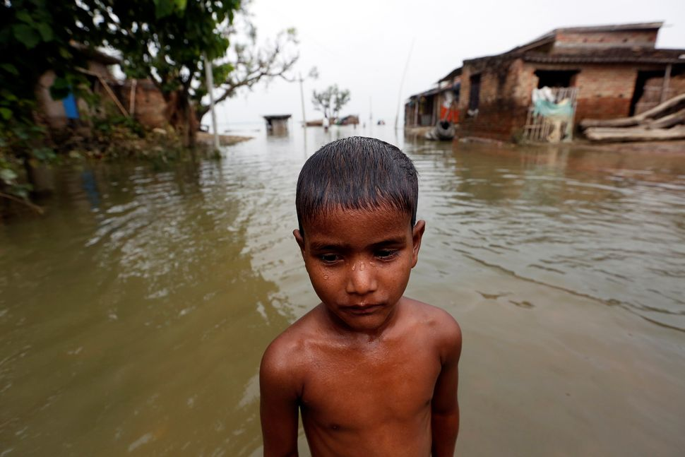 A boy stands in a flooded village in Motihari, Bihar State, on Aug. 23, 2017.