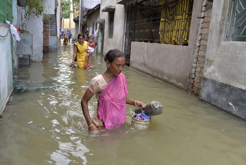 Residents walk through floodwaters in Malda in the state of West Bengal on Aug. 24.