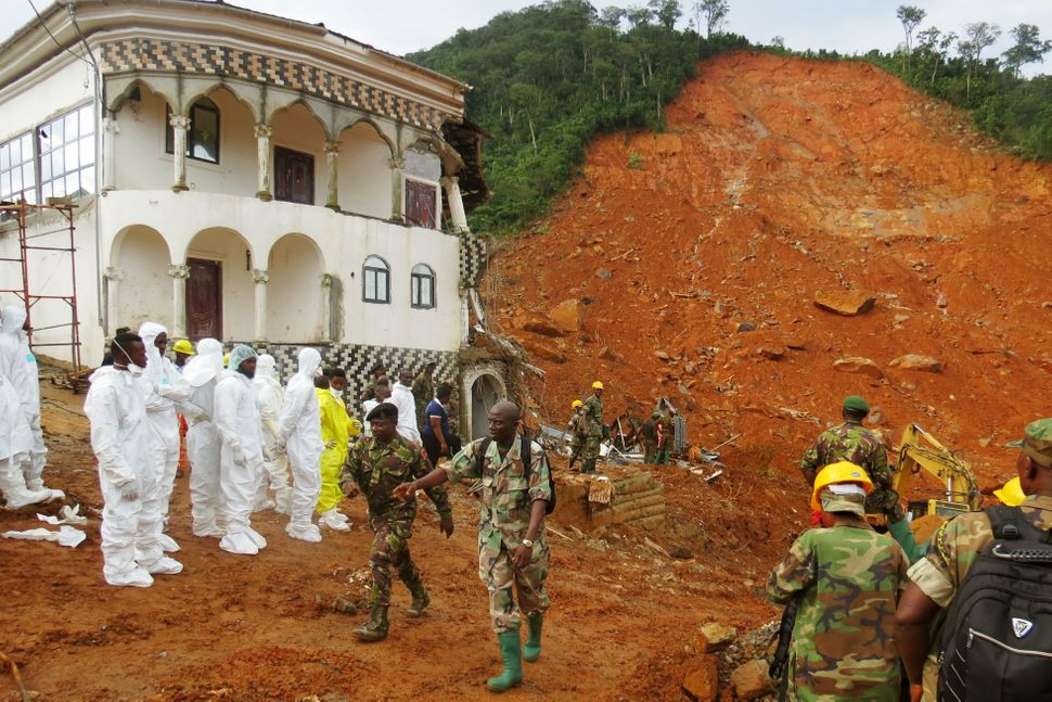 Search-and-rescue team members and soldiers work at the site of a mudslide and damaged building near Freetown on Au