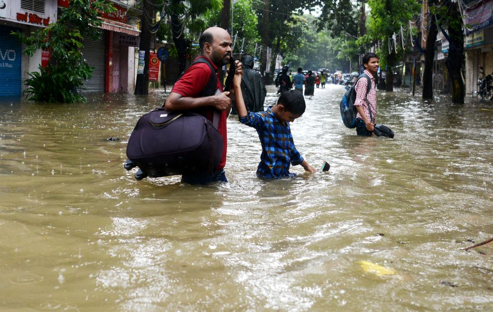 People wade through a flooded street during heavy rain showers in Mumbai on Aug. 29.