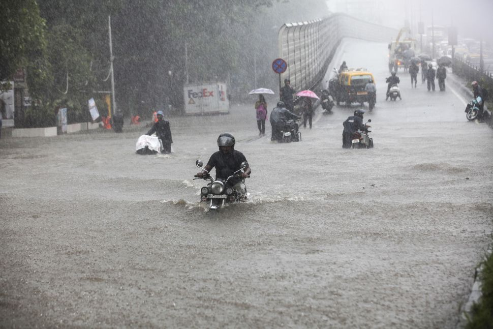 A motorcycle rider wades along a flooded street during heavy rain in Mumbai on Aug. 29.