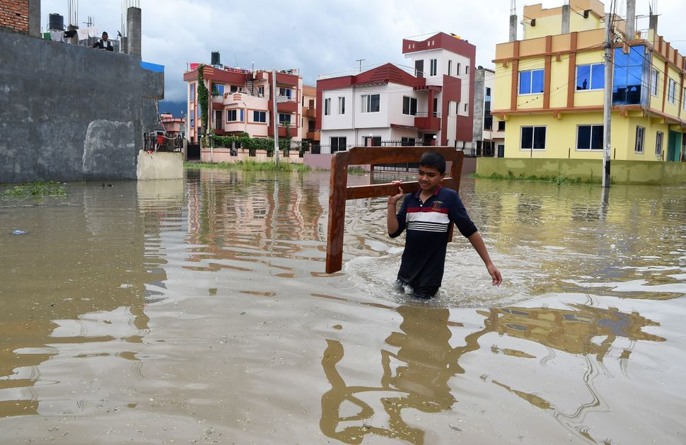 A boy carries goods along a water-logged street in Patan, on the outskirts of Kathmandu, on Aug. 13.