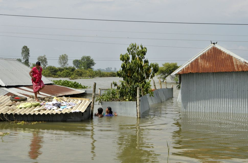 A villager stands atop her partially submerged house in Alal village in West Bengal's Malda district on Aug. 23.
