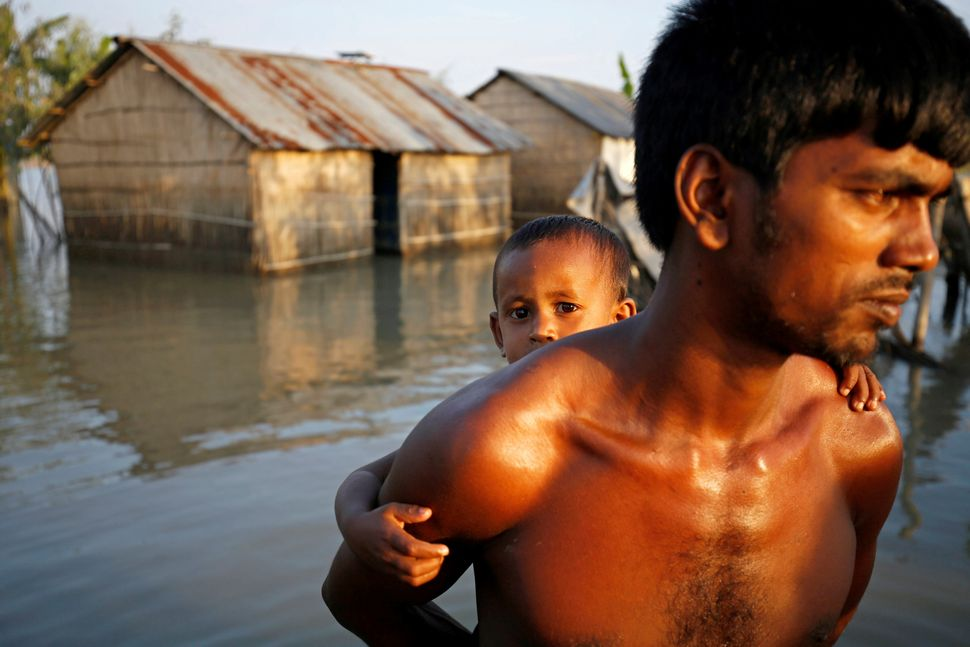 A child is carried on his father's back as they make their way through a flooded area in Bogra on Aug. 20