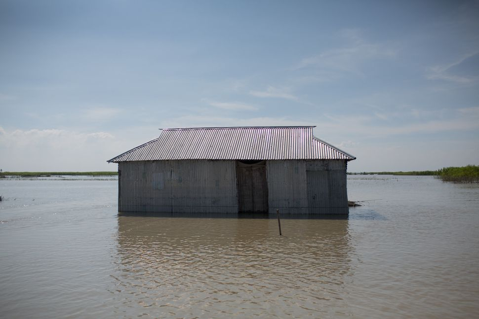 A house is submerged in floodwaters in Sariakandi on Aug. 20.