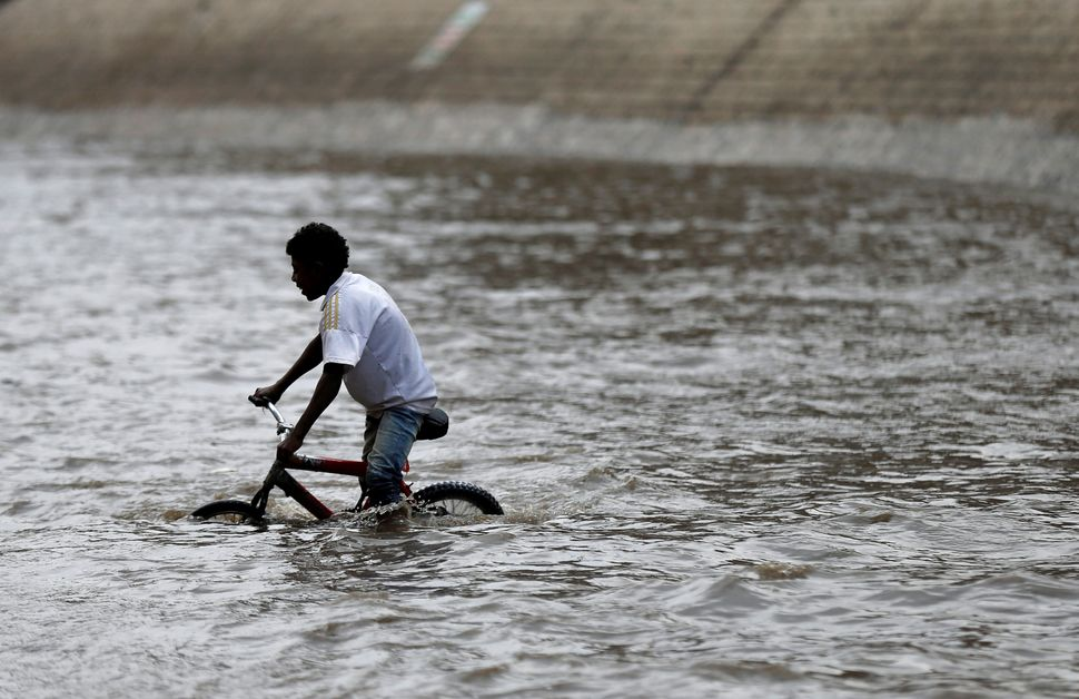A boy rides a bicycle in floodwater in the old quarter of Sanaa on Aug. 9.