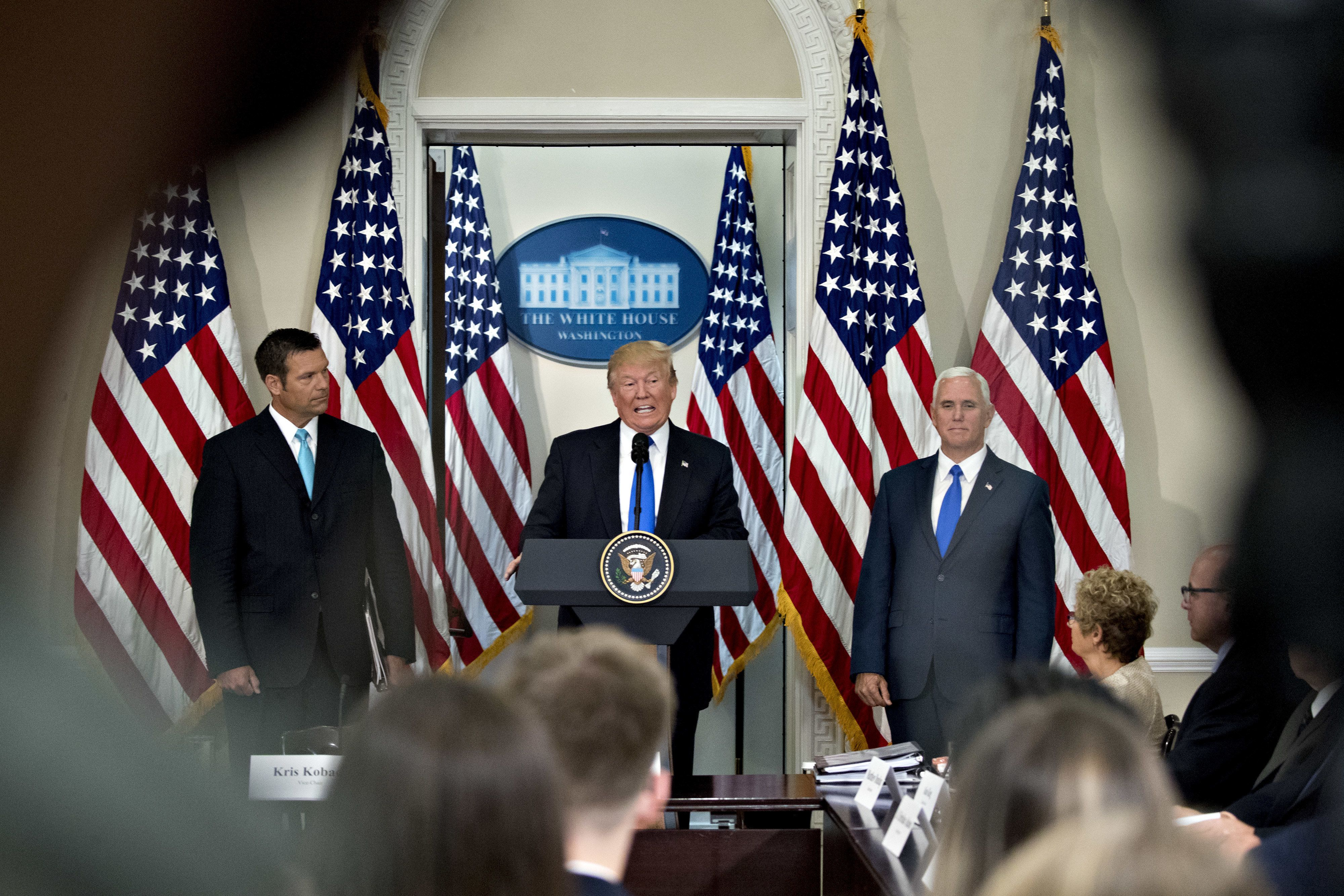 U.S. President Donald Trump, center, speaks as Vice President Mike Pence, right, and Kris Kobach, Kansass secretary of state, listen, during the initial meeting of the Presidential Advisory Commission on Election Integrity at the Eisenhower Executive Office Building in Washington, D.C., U.S., on Wednesday, July 19, 2017. Trump created the advisory commission in May, after claiming without evidence that 3 million people or more illegally voted for Hillary Clinton last year. Photographer: Andrew Harrer/Bloomberg via Getty Images