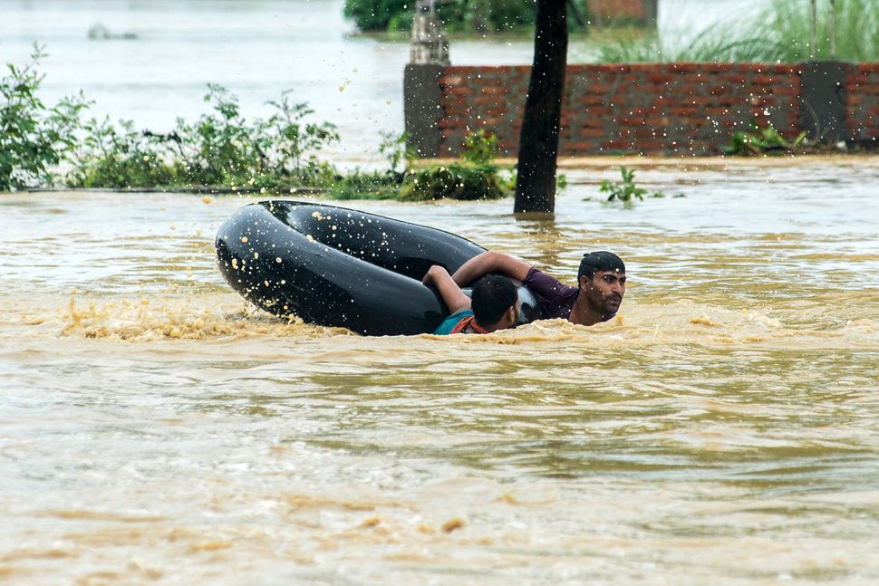 People swim with a rubber ring in a flooded area of the Birgunj Parsa district on Aug. 13.