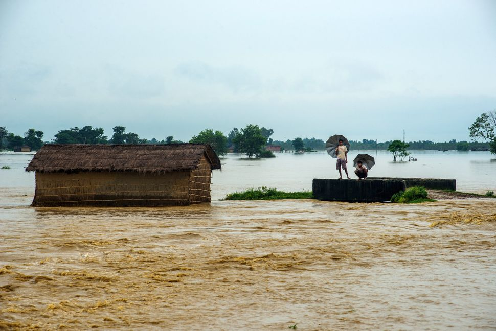 Residents look at the water in a flooded area in Birgunj Parsa on Aug. 13.