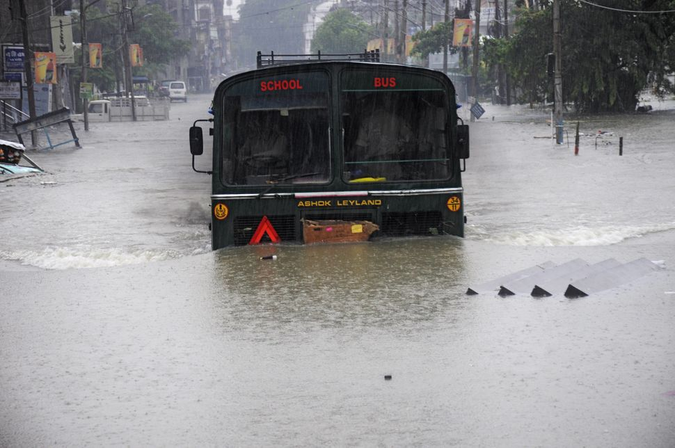 A school bus drives through a flooded street during a heavy downpour in Agartala, the capital of the northeastern state of Tr