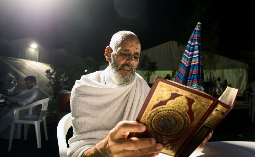 A Muslim pilgrim reads the Quran in the Saudi holy city of Mecca, on the eve of the Day of Arafat -- the climax of the H