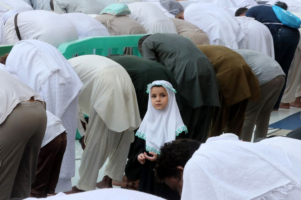 A young girl looks on as Muslim pilgrims pray at the Grand Mosque in the holy Saudi city of Mecca.