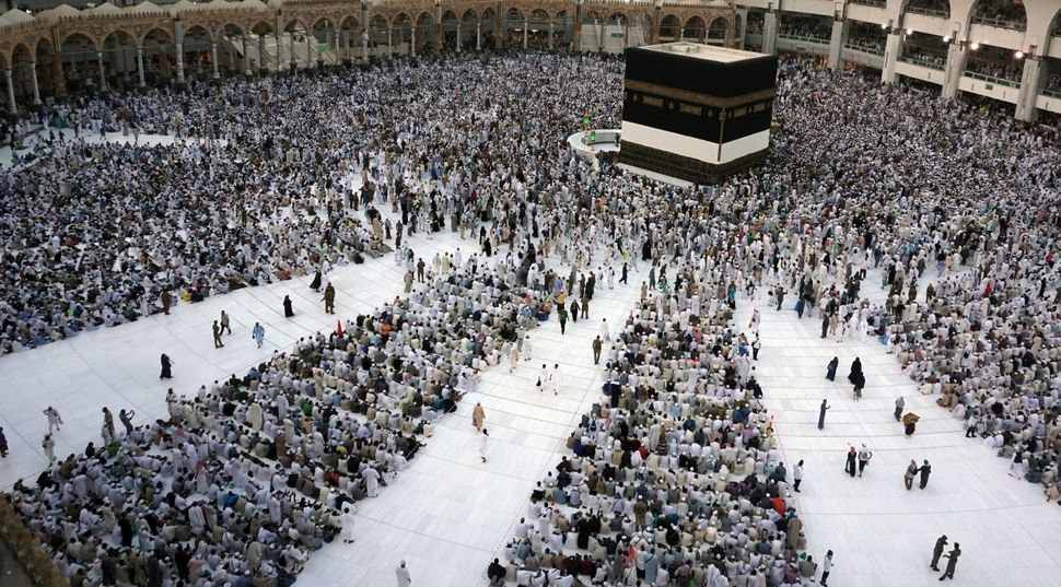 Muslim pilgrims sit and circumambulate around the Kaaba, the cubic building at the Grand Mosque.