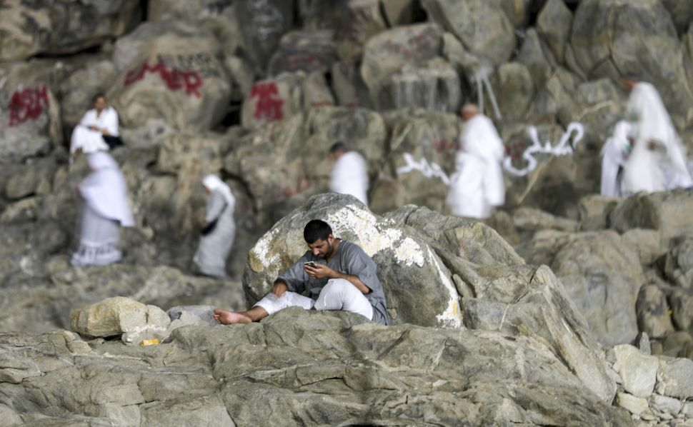 A Muslim man uses his cell phone as pilgrims walk and pray on Mount Arafat, also known as Jabal al-Rahma (Mount of Mercy), so