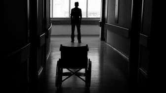 Silhouette of man leaving wheelchair in corridor of hospital.The image was taken in real hospital.Light at the end of corridor is visible for symbolic purpose.Black and white tone is used for effective atmosphere.Photo was shot with DSLR camera.
