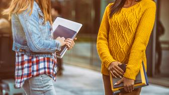 Focus on two unrecognisable female students holding note pads and books standing in front of a modern glass university building.